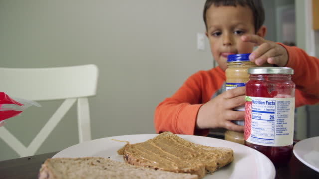 a cute six year-old caucasian boy screws the lid on to a glass jar of peanut butter while making a peanut butter and jelly sandwich at a kitchen table indoors - making a sandwich stock videos and b-roll footage