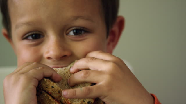 a cute six year-old caucasian boy shows the camera a bite mark in his sandwich before biting it again and smiling - chewing stock videos & royalty-free footage