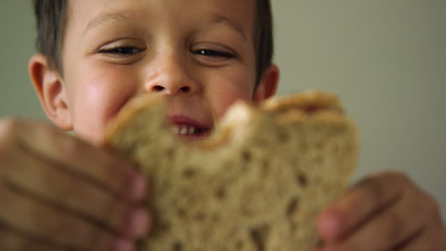 a cute six year-old caucasian boy shows the camera a bite mark in his sandwich before biting it again and smiling - sandwich stock videos & royalty-free footage