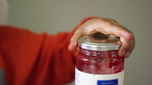a cute six year-old caucasian boy smiles and scrapes jelly off his kitchen knife and on to the side of a glass jelly jar and then replaces the lid while making a peanut butter and jelly sandwich indoors - making a sandwich stock videos and b-roll footage