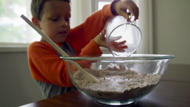 vidéos et rushes de un garçon mignon de six ans caucasien utilise une tasse à mesurer en verre pour verser l'eau dans un grand bol en verre, puis utilise une cuillère en bois pour mélanger les ingrédients pendant la cuisson à une table de cuisine dans une cuisine rés - bricolage