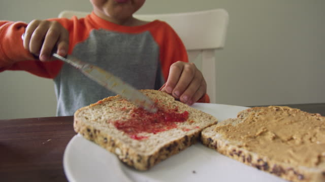 a cute six year-old caucasian boy uses a kitchen knife to scoop jelly from the jar and then to spread it on to a piece of bread sitting on a plate while making a peanut butter and jelly sandwich at a kitchen table indoors - making a sandwich stock videos and b-roll footage
