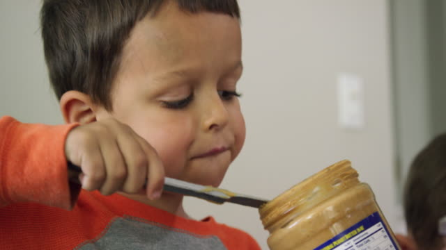 a cute six year-old caucasian boy uses a kitchen knife to scoop peanut butter from a glass jar and then to spread it on to a piece of bread sitting on a plate while making a peanut butter and jelly sandwich at a kitchen table indoors - making a sandwich stock videos and b-roll footage
