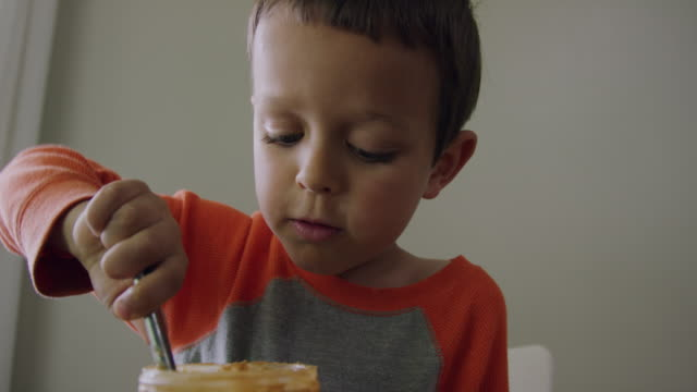 a cute six year-old caucasian boy uses a kitchen knife to scoop peanut butter from a glass jar and then spreads it on to a piece of bread on a plate while making a peanut butter and jelly sandwich at a kitchen table indoors - making a sandwich stock videos and b-roll footage