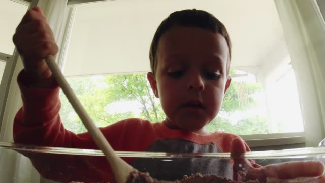 a cute six year-old caucasian boy uses a wooden spoon to mix wet and dry ingredients together in a large, glass bowl while baking in a kitchen indoors - wet wet wet stock videos & royalty-free footage