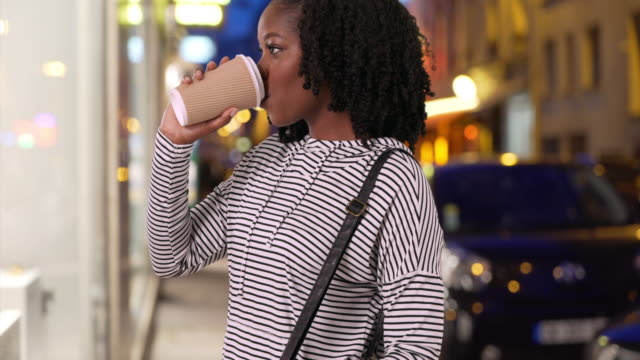 cute smiling female drinking coffee and looking at window display in evening - coffee drink stock videos & royalty-free footage