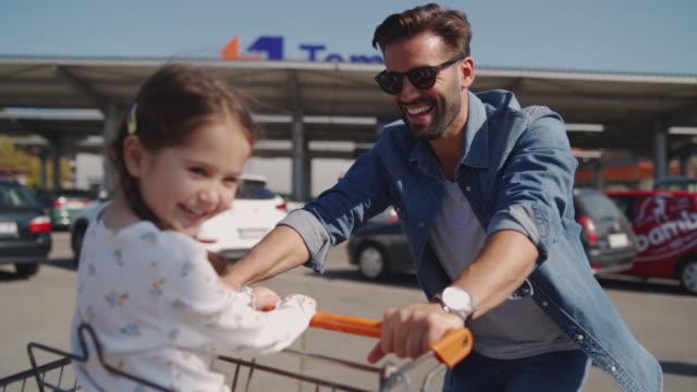 vídeos de stock, filmes e b-roll de menina de sorriso bonito no carro de compra - filha