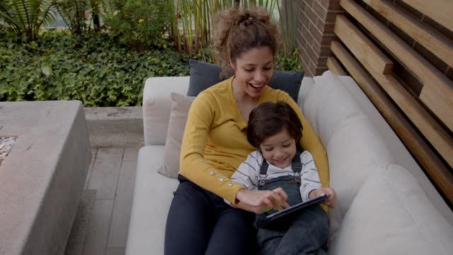 netter sohn und junge mutter mit spaß spielen auf tablet beim entspannen auf der couch - patio stock-videos und b-roll-filmmaterial