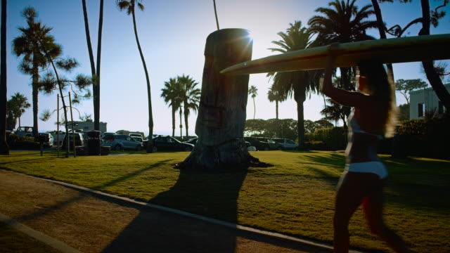 vídeos y material grabado en eventos de stock de una linda surfista walks down a la playa con su tabla de surf, usa una monada biquini en el sol de verano. - pipeline wave