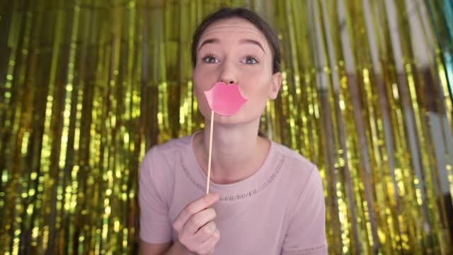 かわいい十代の少女は唇の小道具で楽しんで、フォトブースで自分撮りを取る - 口を尖らせる点の映像素材/bロール