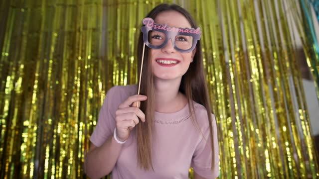 stockvideo's en b-roll-footage met leuk tienermeisje dat pret met steun heeft en selfie op fotocabine neemt - image