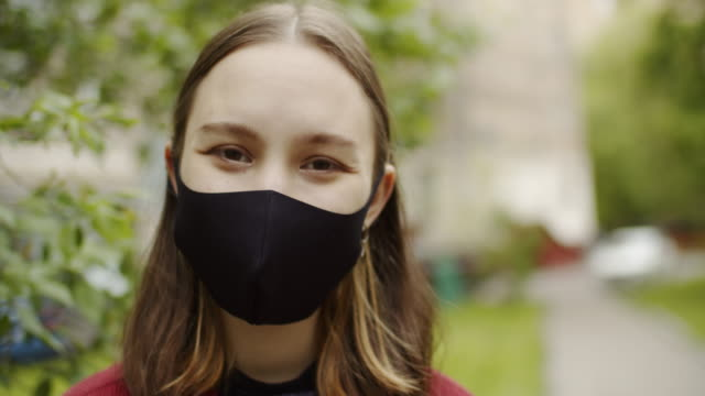 cute teenage girl smiling behind protective mask outdoors - 18 19 years stock videos & royalty-free footage