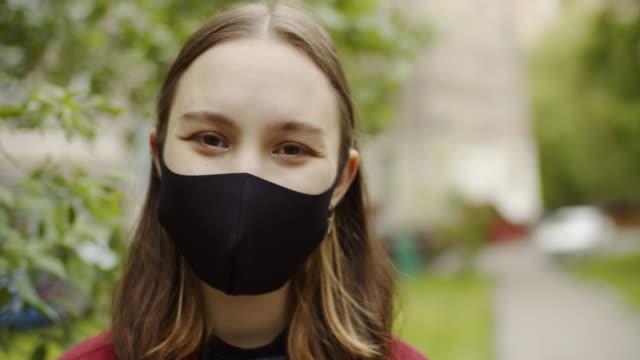 vídeos de stock e filmes b-roll de cute teenage girl smiling behind protective mask outdoors - flexibilidade