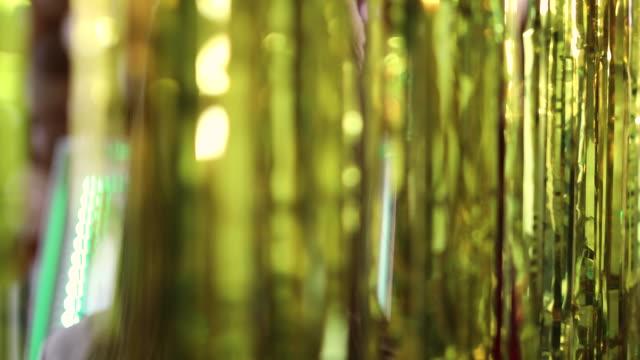 パーティーで金色のメタリックホイルカーテンの後ろに立っているかわいい十代の少女 - アルミホイル点の映像素材/bロール