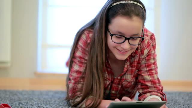 cute teenage girl with eye glassesd using digital tablet - t shirt stock videos & royalty-free footage