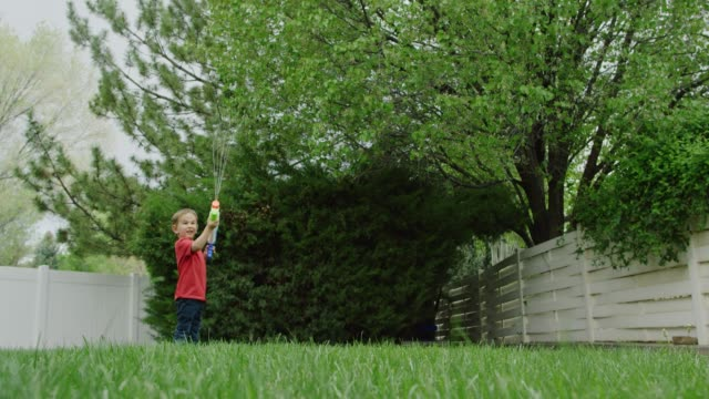 a cute three year-old caucasian boy shoots water from his toy water gun in a green backyard with trees and grass - toy gun stock videos & royalty-free footage