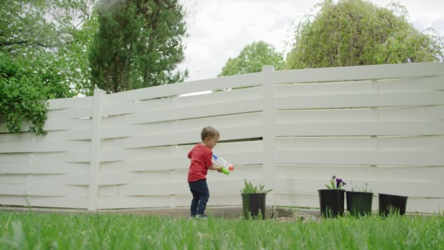 a cute three year-old caucasian boy uses his toy water gun to water irises in buckets in a green backyard with trees and grass - toy gun stock videos & royalty-free footage