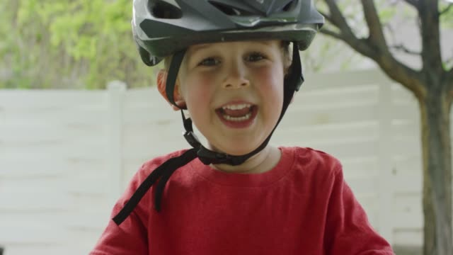 a cute three year-old caucasian boy wearing a bicycle helmet smiles and laughs outdoors while standing over his bike - handlebar stock videos & royalty-free footage