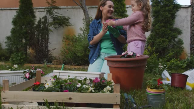 vidéos et rushes de enfant en bas âge mignon aidant sa mère dans le jardinage - gant de jardinage