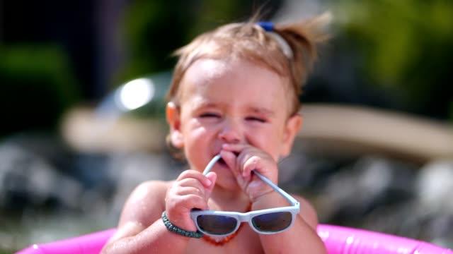 vidéos et rushes de garçon mignon bambin jouant dans une piscine gonflable - pataugeoire