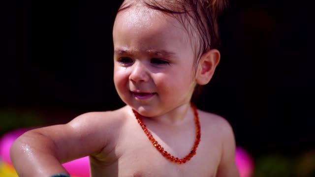 vidéos et rushes de garçon mignon bambin jouant dans le back yard - pataugeoire