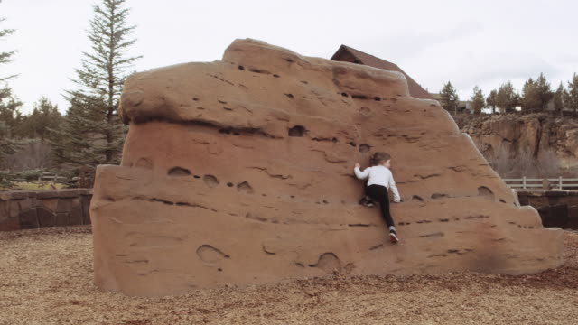 Cute toddler daughter playing on rock feature