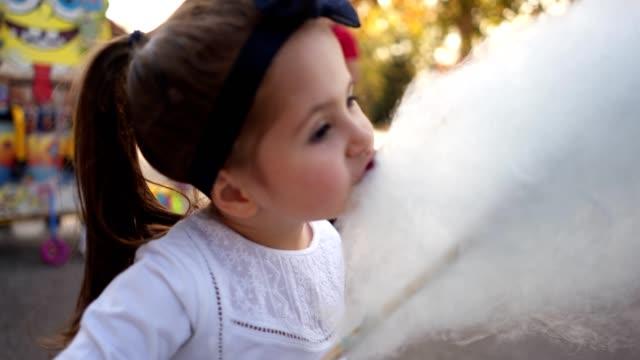 niedlichen kleinkind essen zuckerwatte in einem park - zucker stock-videos und b-roll-filmmaterial