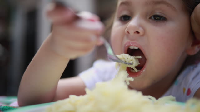cute toddler eating spaghetti at home with a fork - spaghetti alla bolognese video stock e b–roll