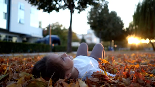 Cute toddler girl lying in fallen leaves in sunset