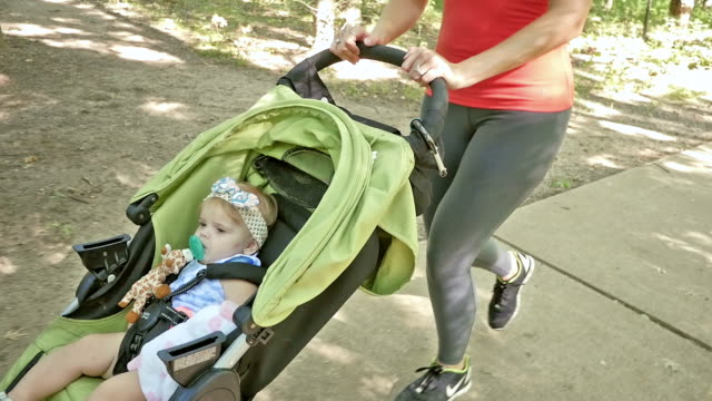 cute toddler girl riding in jogging stroller while mom runs behind her - three wheeled pushchair stock videos & royalty-free footage