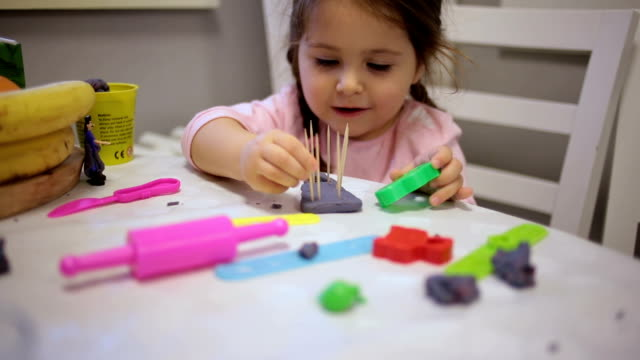 Cute toddler playing with child's clay
