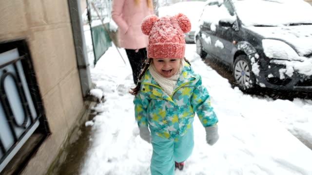 vídeos de stock e filmes b-roll de cute toddler running in snow while mother is waiting - língua de fora