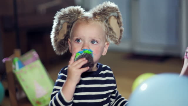 cu cute toddler wearing furry bunny ears eating cupcake / santa monica, ca, united states     - cupcake stock videos & royalty-free footage