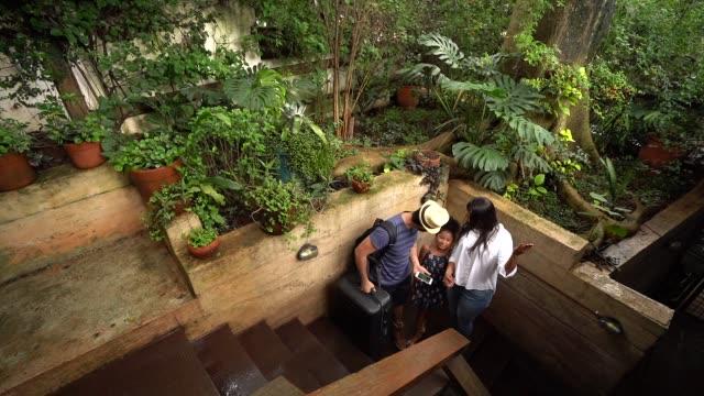 vídeos y material grabado en eventos de stock de familia linda viajero al llegar a la casa de huéspedes con móvil - alojamiento y desayuno