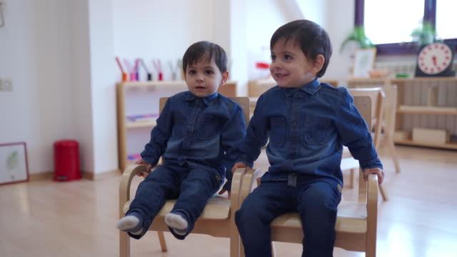 vídeos de stock, filmes e b-roll de irmãos gêmeos fofos curtindo um tempo juntos em sala de aula de cuidados infantis - cadeira