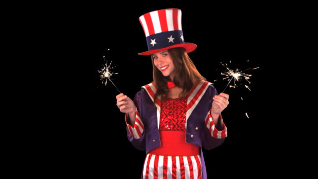 cute uncle sam girl with sparklers - this clip has an embedded alpha-channel - pre matted stock-videos und b-roll-filmmaterial