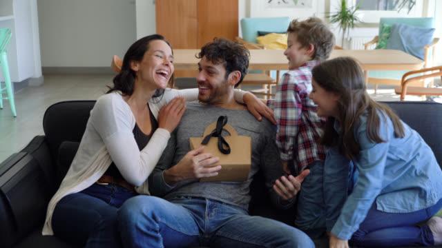 vídeos y material grabado en eventos de stock de bonita esposa y niños sorprendente hombre sentado en el sofá con el teléfono inteligente con el regalo del día del padre - father day