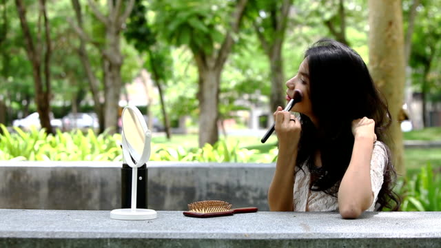 vidéos et rushes de peigne son joli femme coiffure et de maquillage à son visage dans le jardin - bouche humaine