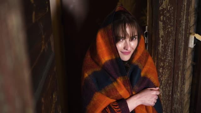 vídeos y material grabado en eventos de stock de cute woman in warm cozy plaid looks at you at wooden house - tartán