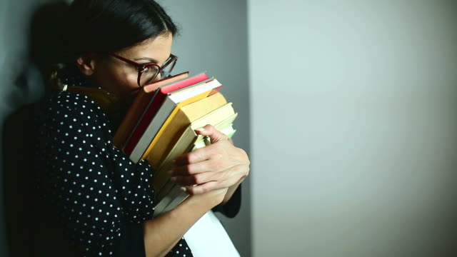 cute woman peeking behind books, changing emotions - shy stock videos & royalty-free footage