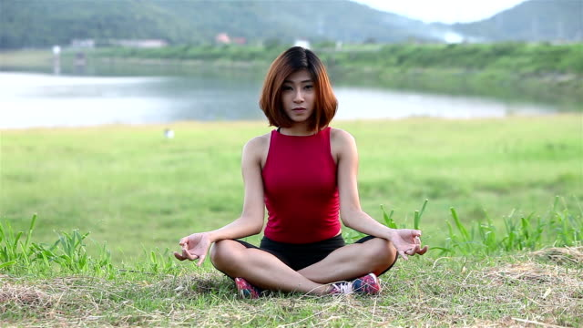 cute woman practicing lotus pose on lawn and smile,dam and mountain background - mountain pose stock videos and b-roll footage