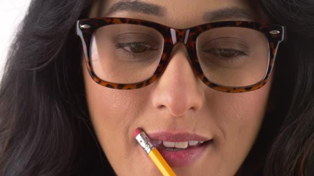 vídeos de stock, filmes e b-roll de cute woman wearing glasses and biting pencil - lápis
