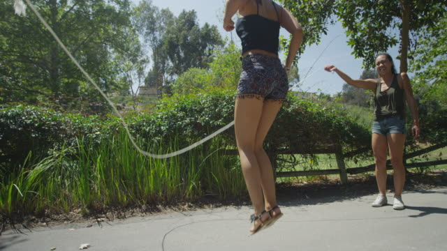 cute women jumping rope at the park - skipping along stock videos & royalty-free footage