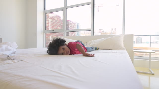 cute young black boy jumping on bed - stabilisers stock videos & royalty-free footage