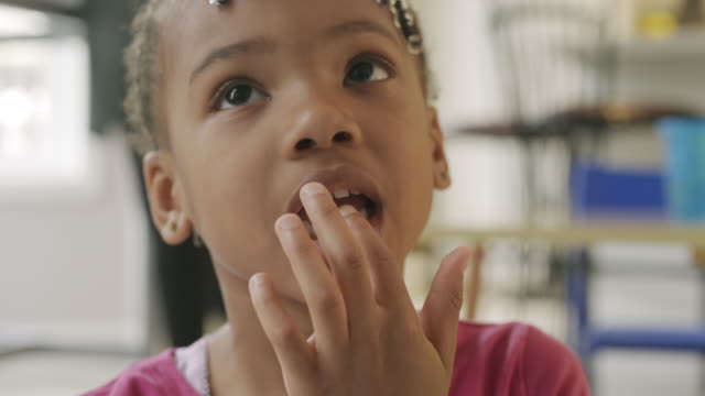stockvideo's en b-roll-footage met cute young black girl smiling into camera showing her loose tooth. - alleen meisjes