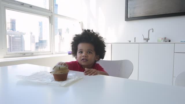 cute young boy eating muffin at table in modern loft. - 少年一人点の映像素材/bロール