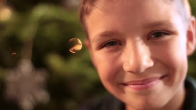 cute young boy looks up and smiles at camera in front of christmas tree - hope stock videos & royalty-free footage