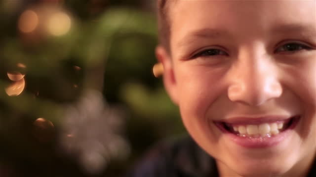Cute young boy smiles at camera in front of Christmas tree