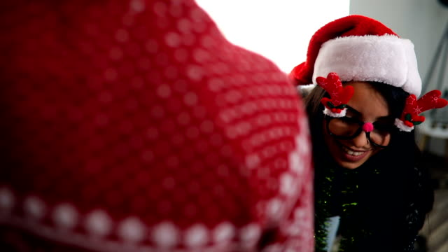 süßen, jungen paar einen weihnachtsbaum zu verzieren - weihnachtsmütze stock-videos und b-roll-filmmaterial