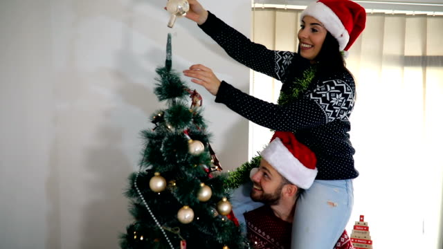 cute, young couple decorating a christmas tree - decorating the christmas tree stock videos & royalty-free footage